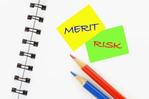 メリット、リスクと書かれた付箋と赤青えんぴつ